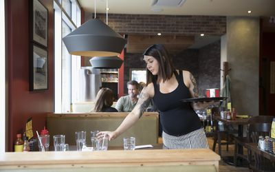 Pregnant waitress bussing table in restaurant