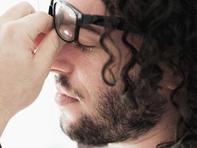 Stressed man rubbing his eyes