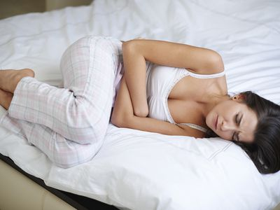 woman with stomach pain on bed
