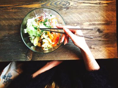 woman's hands holding chopsticks in bowl of food