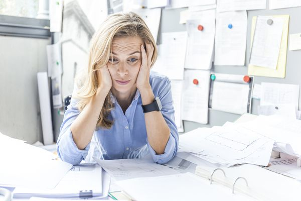 Woman with her head in her hands looking stressed at work