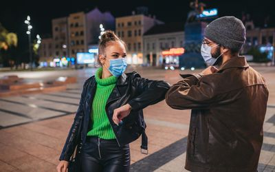 Two adults wearing masks and greeting each other by touching elbows