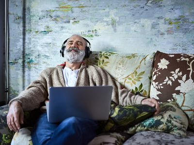 A man sitting on the couch, relaxing with headphones on