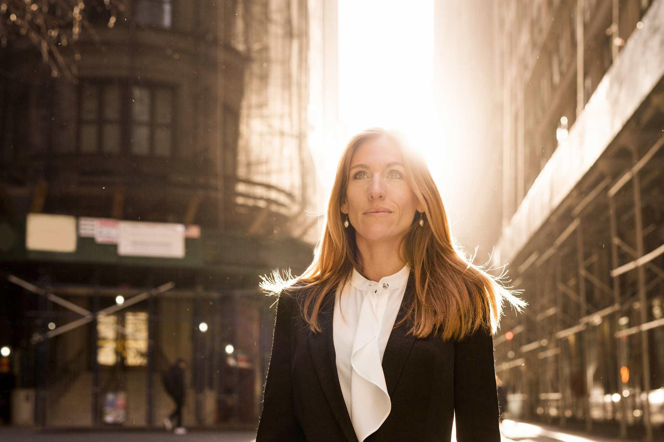 Businesswoman standing on city street with sunlight shining