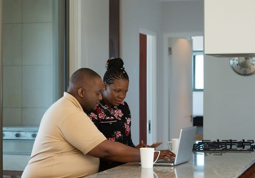 A couple sitting at their home trying to do their finances on a laptop. They are in discussion with one another.