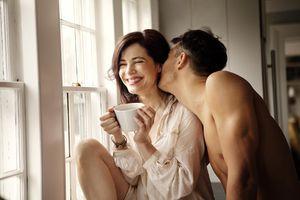 Man kissing, teasing woman over coffee