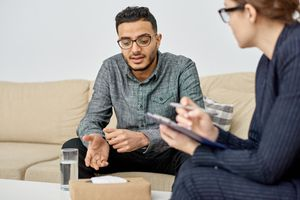 Person in counseling session sits on couch in therapist office.