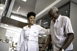 A caretaker wearing a white coat helps a man using a walker. Both people are smiling.
