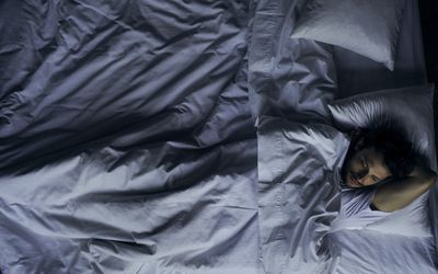 A photograph of a man lying awake in a rumpled bed.