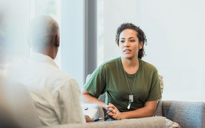 A serious mid adult female soldier talks to a male mental health professional about hard situations while serving overseas.