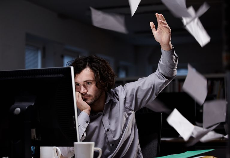 Office worker working late, throwing paper in the air