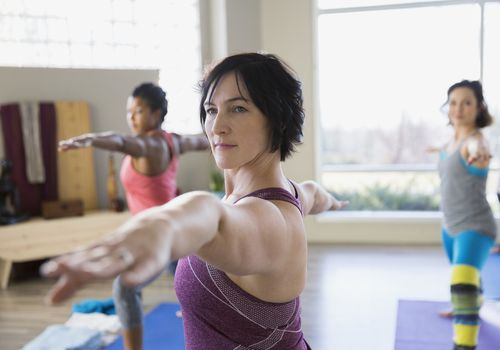 Woman doing a yoga pose in a class with other women in the background