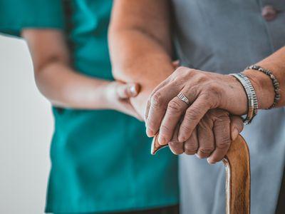 woman in nursing home helping elderly woman
