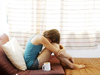 upset woman curled in ball in front of window at home