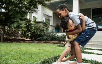 Two young boys playing in the front yard of a house