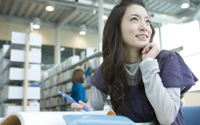 smiling young woman studying in library