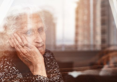 Elderly woman sitting alone and looking sadly outside the window