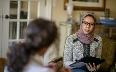 Woman in hijab holding a therapy session with a female client