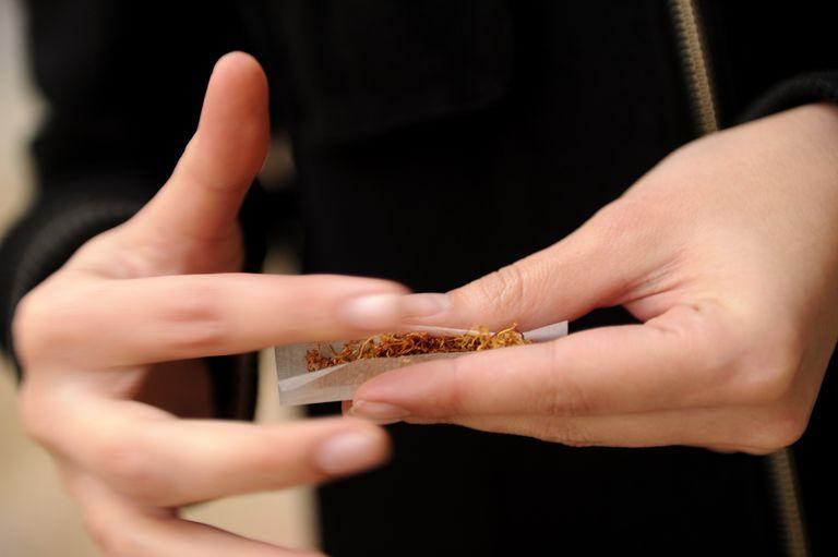 Person hand rolling a cigarette.