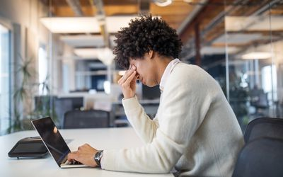 Man working late at his computer feeling stressed