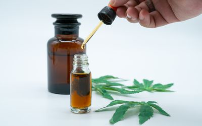 Hand holding bottle of Cannabis oil in pipette