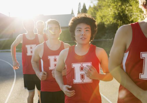 High school boys on sports team running outdoors
