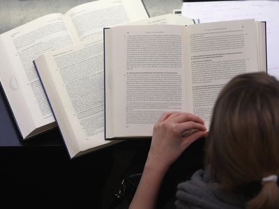 Woman reading from several books open in front of her