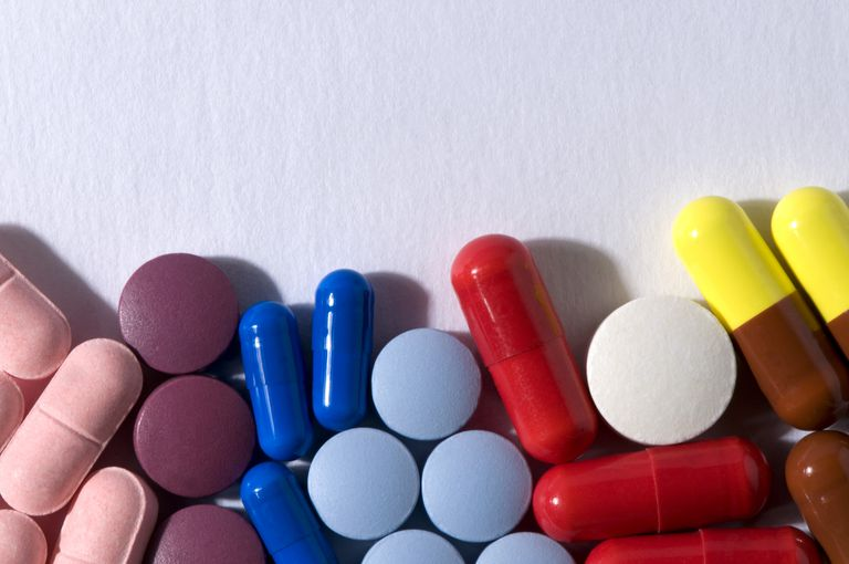 colorful multi-shaped pills on white table