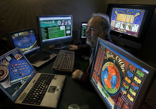 Senior man surrounded by 6 different screens of online poker