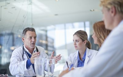 A team of doctors meets in a conference room.