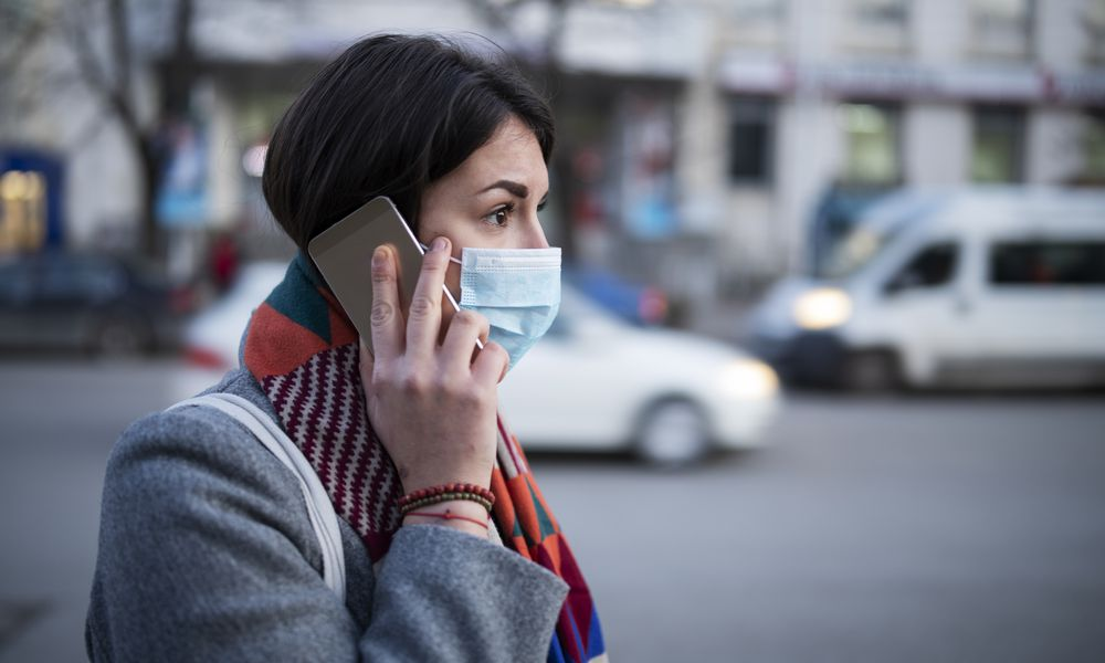 Young Woman With Face Mask Talking On The Phone