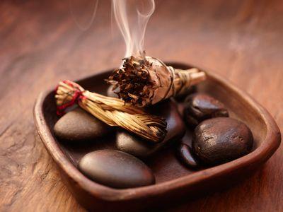 Bowl of rocks with burning sage.