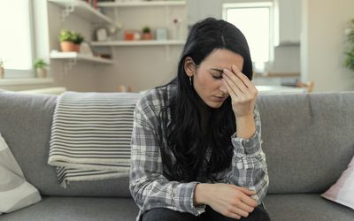 Frustrated young woman suffering from the headache while sitting on the sofa at home with an expression of being unwell, with eyes closed.