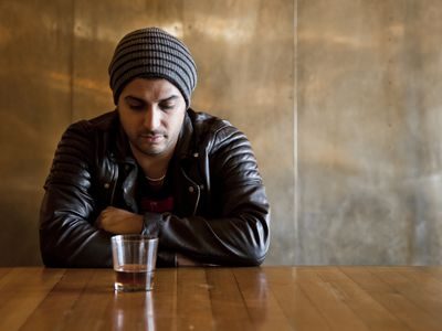 Depressed looking man sitting at table with a glass of liquor