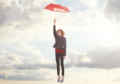 Woman holding open umbrella and ascending into sky