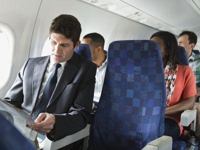 Businessman reading newspaper in airplane