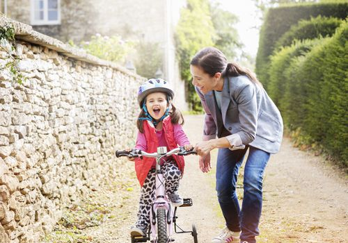 woman helping young girl learn how to ride bicycle