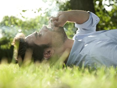 Young man laying in grass smoking marijuana