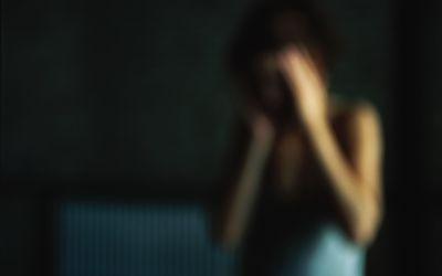 Woman holding head, defocused