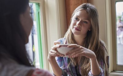 Two girls talking and having tea in cafe