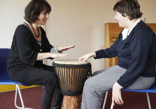 A music therapist and her patient drum together