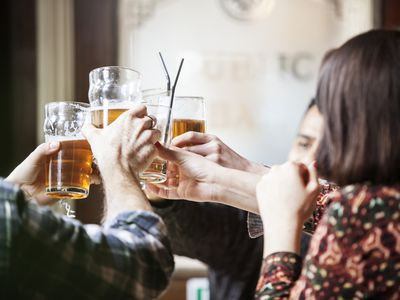 A group of friends toasting with beer mugs at a pub