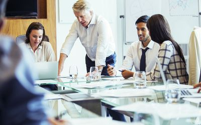 business people working and talking around conference room table