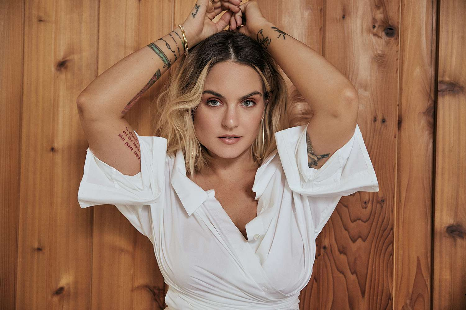 JoJo in a white top with hands above her head