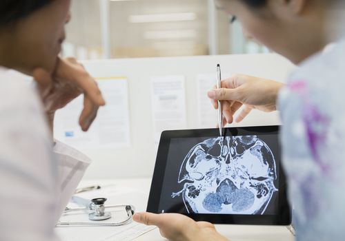 Doctor and nurse examining CT scan digital tablet