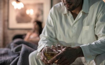 Man sitting on bed having a drink