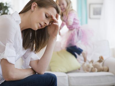 Stressed woman with daughter jumping behind her