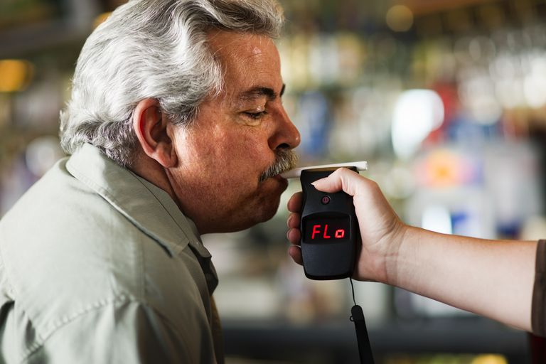 man blowing into breathalyzer test