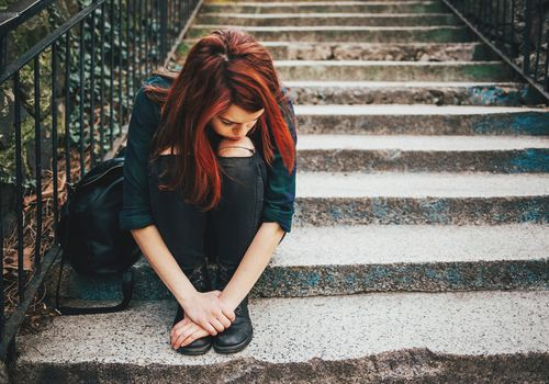 A woman seated on concrete stairs with her chin resting on her knees.