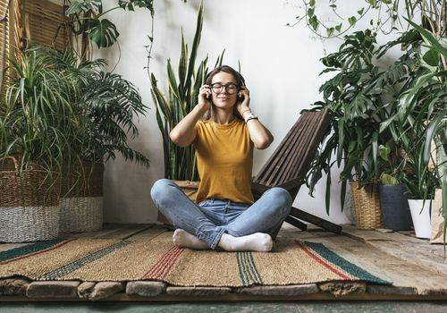 Relaxed young woman sitting on the floor at home listening to music